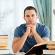 Student sitting at his desk thinking — Stockfoto
