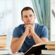 Student sitting at his desk in thoughts - Foto Stock