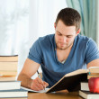 Student working through his books - Stockfoto
