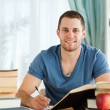 Smiling student working on his book report — Stockfoto