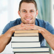 Smiling student leaning on his books - Stockfoto