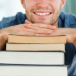 Close up of student with a pile of books — Stock Photo