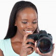 Smiling young photographer having a look at her camera — Stock Photo #11202148