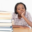 Bored student looking at a stack of books — Stock Photo