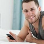 Smiling man using his mobile phone — Stock Photo