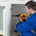 Young handyman fixing a door — Stock Photo