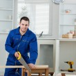 Portrait of a smiling handyman cutting a wooden board — Stock Photo