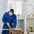 Portrait of a handsome handyman cutting a wooden board — Stock Photo
