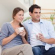Couple watching TV while drinking tea — Stock Photo