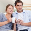 Portrait of a couple drinking coffee while watching TV — Stock Photo