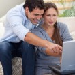 Portrait of a startled couple using a laptop — Stock Photo #11204298