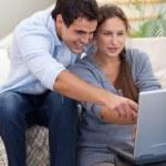 Retrato de una pareja sorprendida usando una laptop — Foto de Stock
