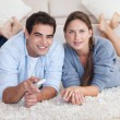 Lovely couple watching TV while lying on a carpet — Stock Photo