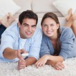 Smiling couple watching TV while lying on a carpet — Stock Photo #11204434