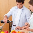 Portrait of a man pouring a glass of wine while his wife is cook — Stock Photo #11204480