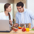 Couple using a notebook to cook - Stock Photo
