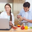 Young couple using a notebook to cook — Stock Photo