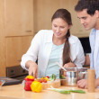 Happy couple using a laptop to cook — Stock Photo