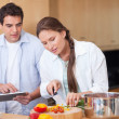 Modern couple using a tablet computer to cook — Stock Photo