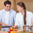 Charming couple using a tablet computer to cook — Stock Photo