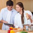 Stock Photo: In love couple using a tablet computer to cook