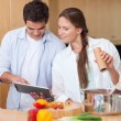 In love couple using a tablet computer to cook — Stock Photo