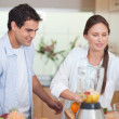 Portrait of a young couple making fresh fruits juice — Stock Photo