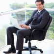 Portrait of a young businessman sitting on an armchair working w — Stock Photo