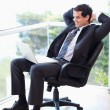Portrait of a relaxed businessman sitting on an armchair working — Stock Photo