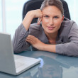 Beautiful businesswoman leaning on her desk — Stock Photo #11204748