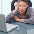 Serious businesswoman leaning on her desk — Stock Photo #11204749