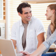 Smiling couple with laptop in the kitchen — Stock Photo