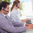 Stock Photo: Call center agents working next to each other