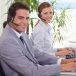 Stock Photo: Side view of smiling call center agents