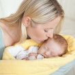 Affectionate mother kissing her baby's forehead — Stock Photo