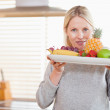 Woman holding a plate of fruits — Stock Photo