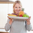 Woman presenting plate of fruits — Stock Photo