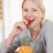Close up of smiling woman having a strawberry — Stock Photo