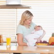 Woman holding her sleeping baby in the kitchen — Stock Photo #11205681