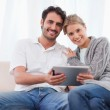 Charming couple using a tablet computer — Stock Photo