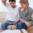Portrait of a couple looking at their bills - Stock Photo