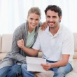 Delighted couple reading a letter — Stock Photo #11205853