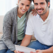 Portrait of a smiling couple reading a letter - Stock Photo