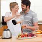 Young couple making fresh fruits juice — Stock Photo #11206062