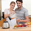 Young couple making fruits juice — Stock Photo