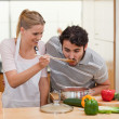 Charming couple preparing a sauce - Stock Photo