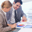 Portrait of smiling business studying statistics — Stock Photo