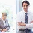 Young businessman posing while his colleague is working — Stock Photo