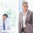 Businesswoman posing while her colleague is working — Stock Photo #11206372