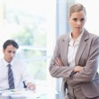 Serious businesswoman posing while her colleague is working — Stock Photo #11206374